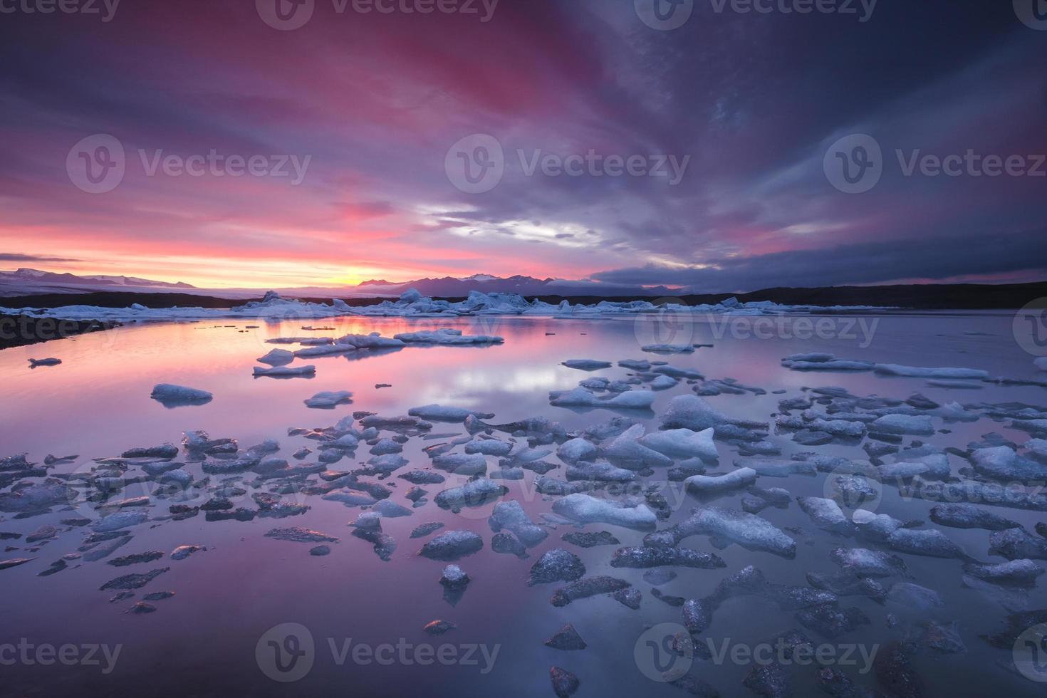 isberg som flyter i fjallsarlon glaciärsjön vid solnedgången foto