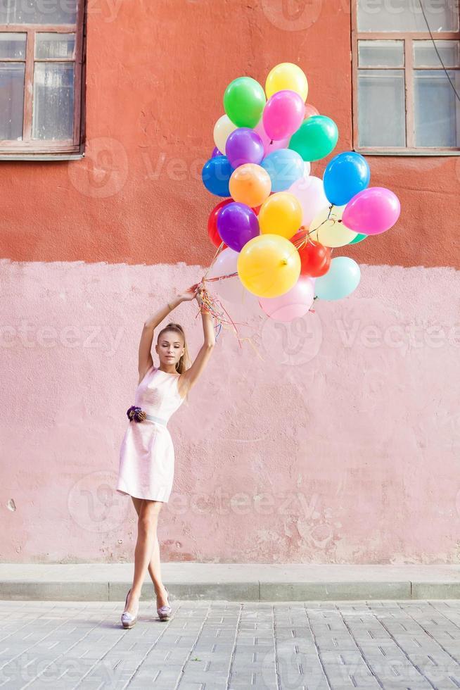 ung kvinna som håller massa färgglada ballonger på gatan foto