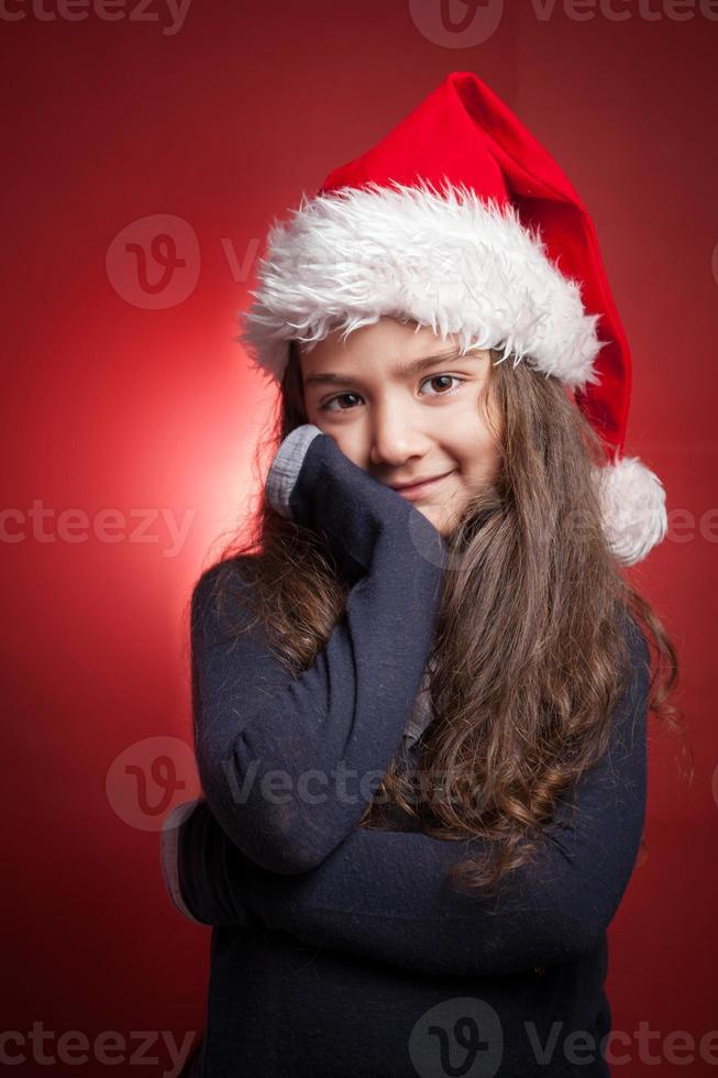 liten flicka i röd santa hatt på röd bakgrund foto