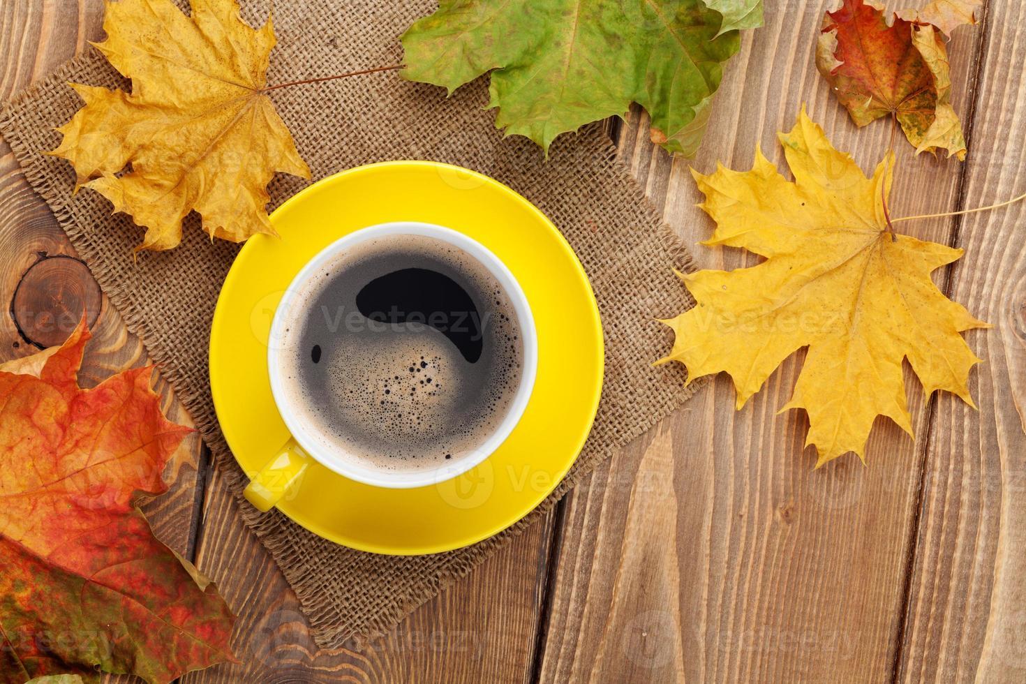 höstlöv och kaffekopp över träbakgrund foto