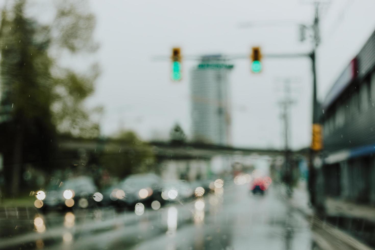 defokuserade bilar vid ett trafikljus en regnig dag foto