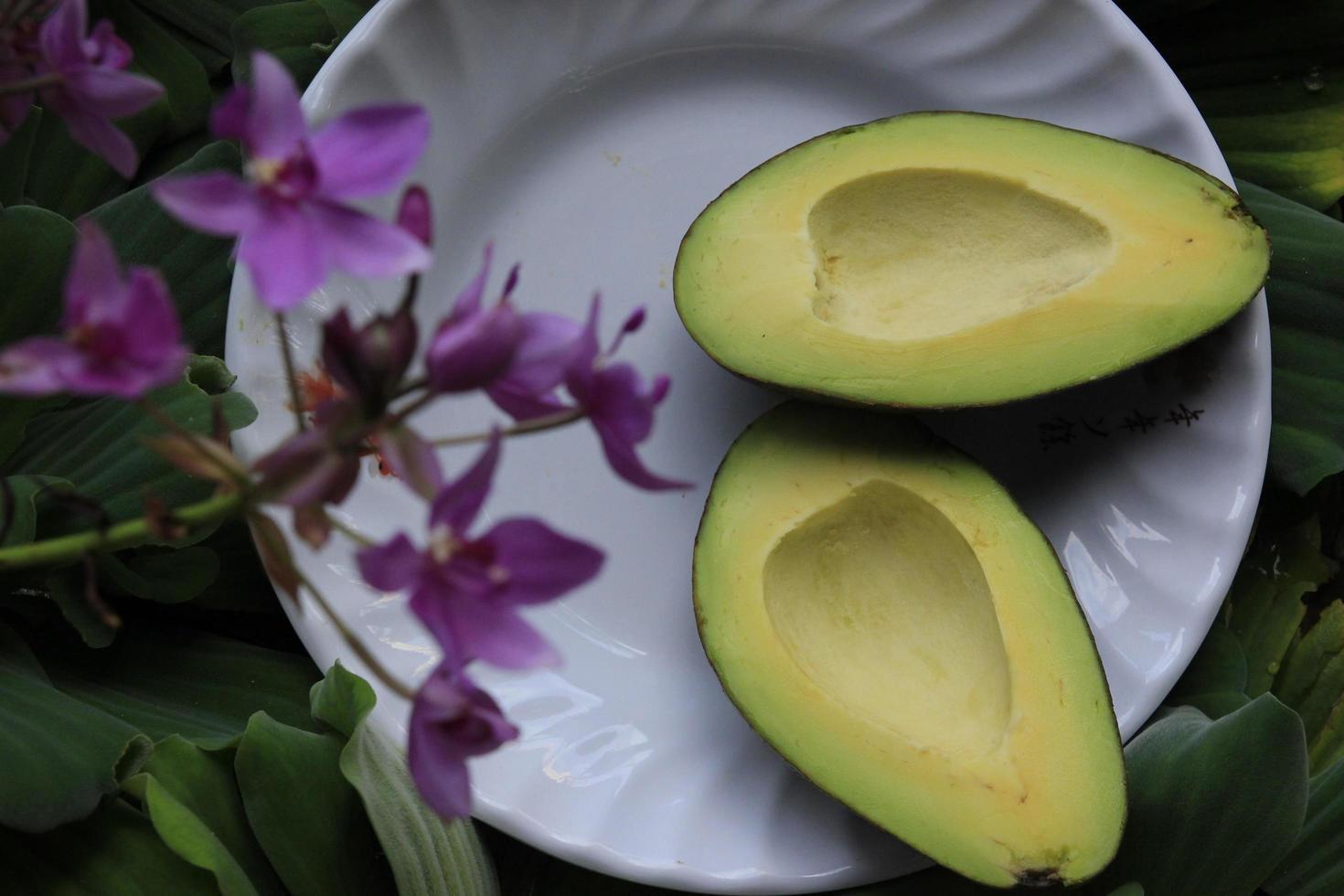 skivad avokado på vit keramisk platta foto