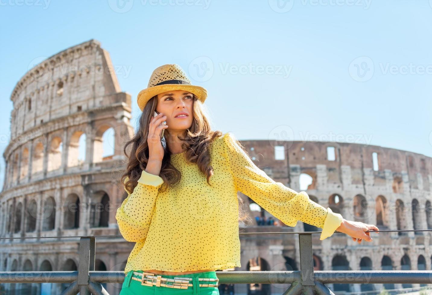 ung kvinna som talar mobiltelefon nära colosseum i Rom, Italien foto