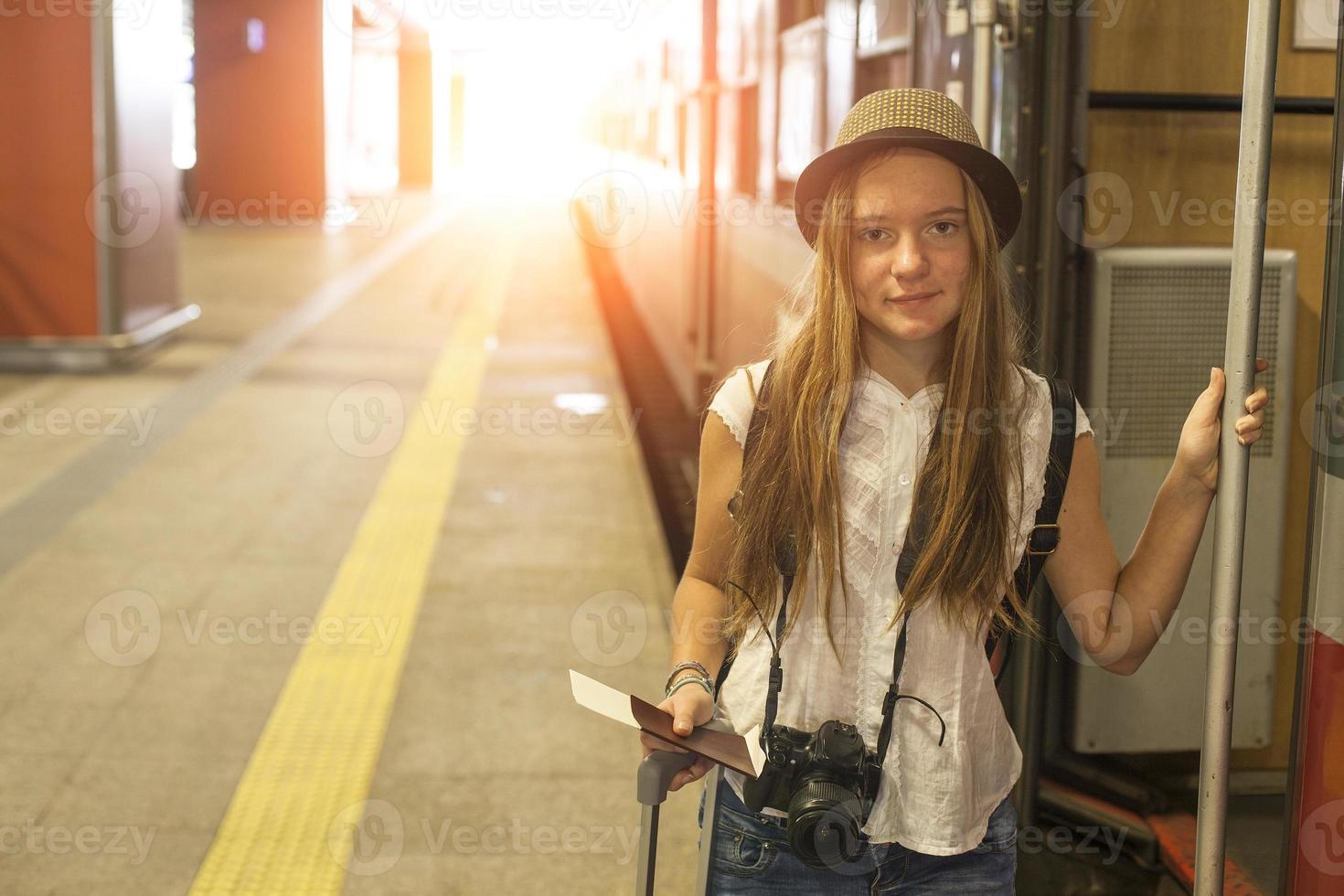 ganska ung flicka som går ombord på ett tåg på en järnvägsstation. foto
