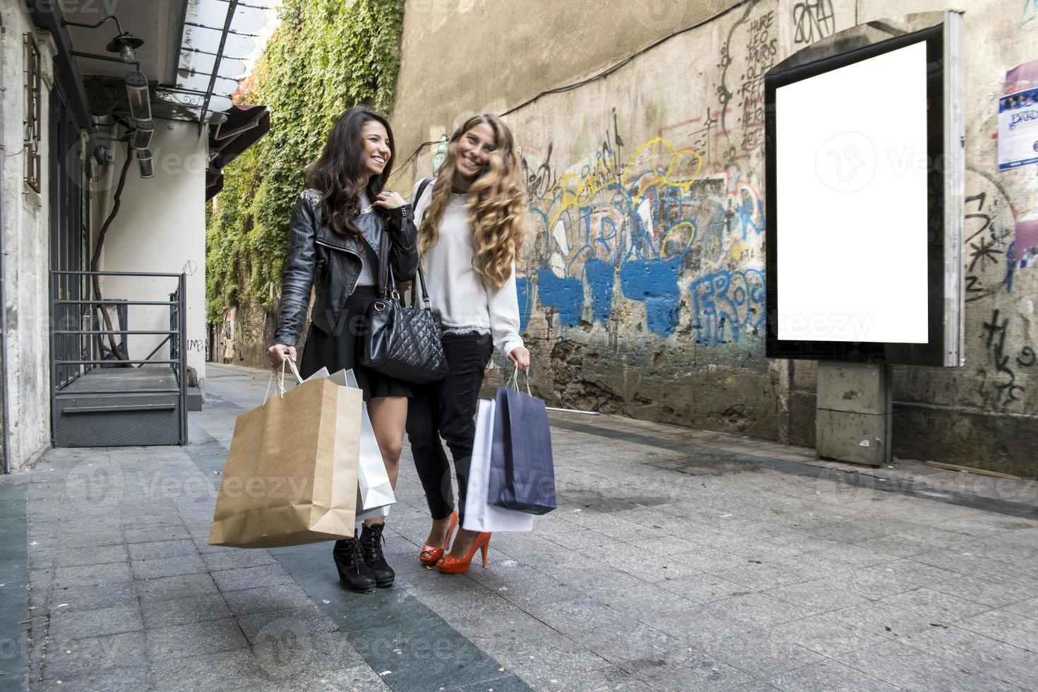 två tjejer pratar och går foto