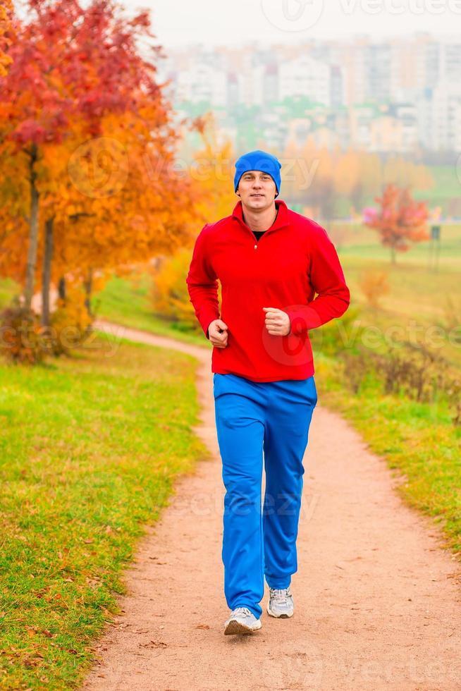 manlig idrottare som joggar på morgonen i parken foto