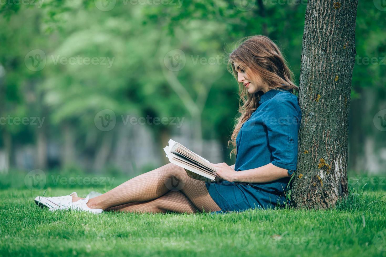 flicka som läser en bok i park foto