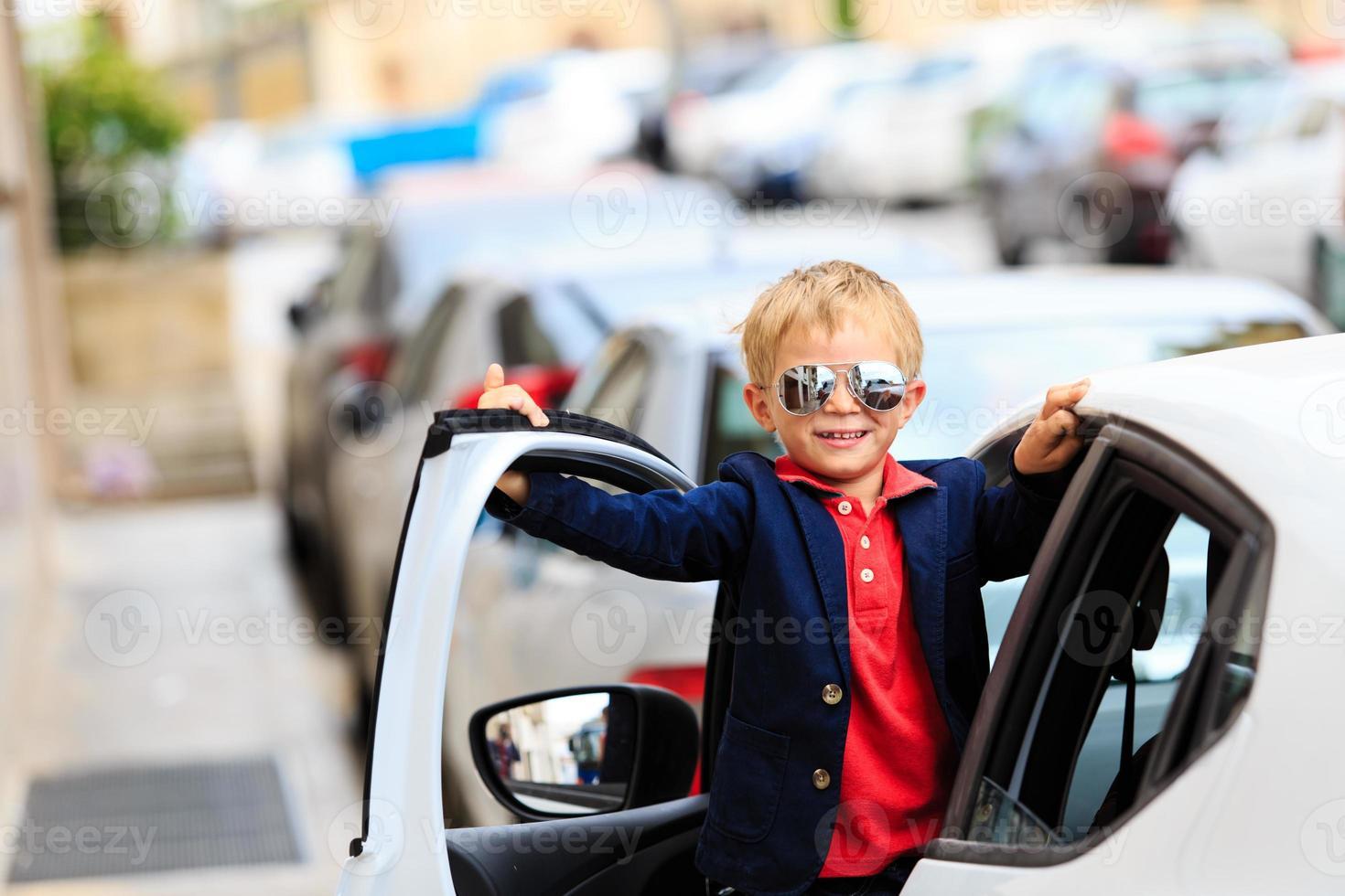 liten pojke reser med bil i staden foto