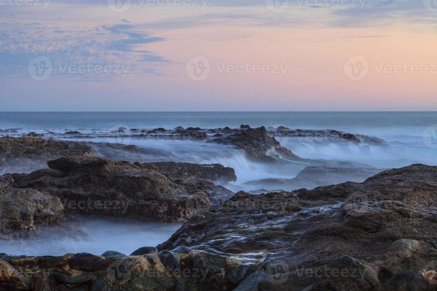 solnedgång över klipporna i lagunastranden foto
