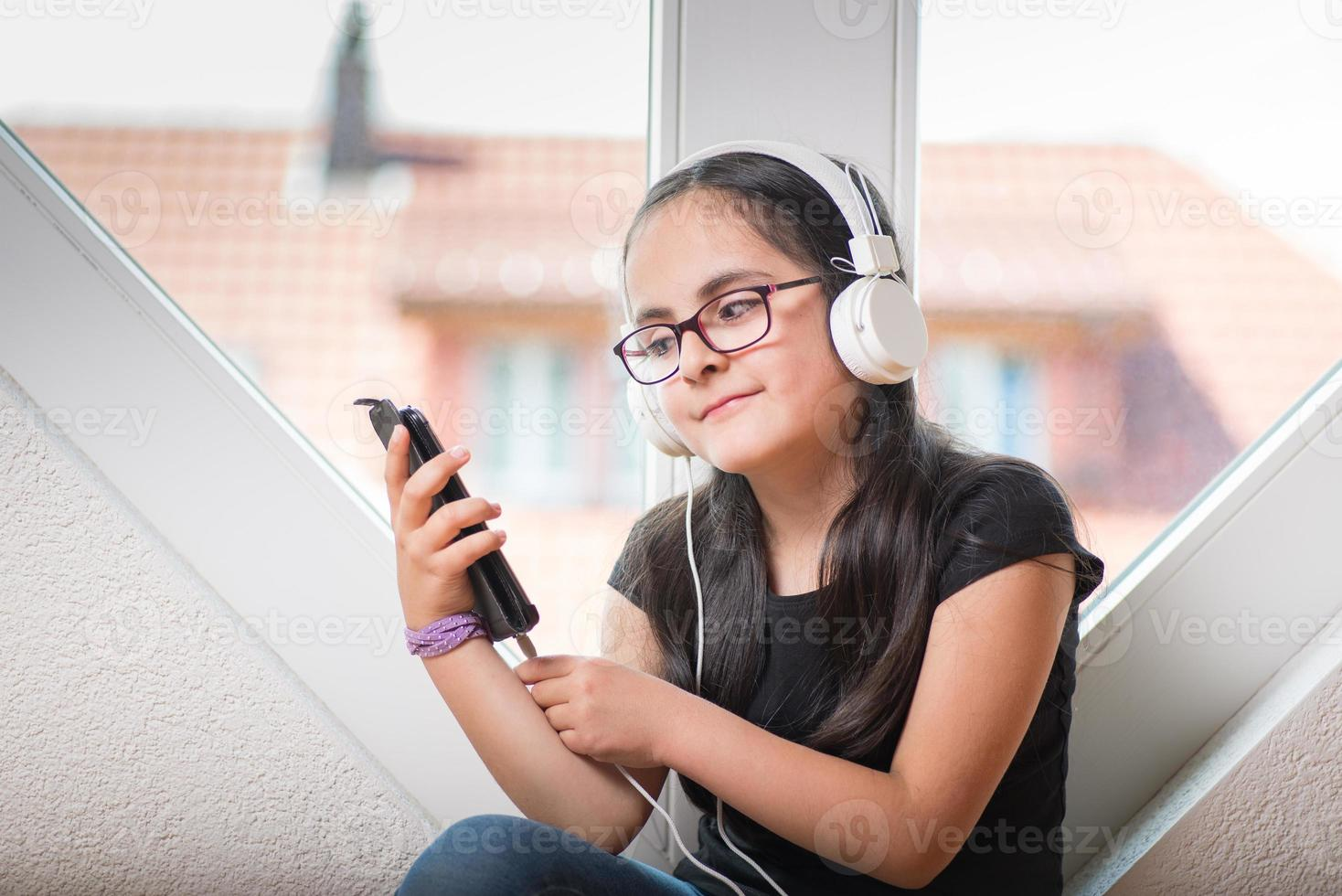 söt tjej med glasögon som lyssnar på musik foto