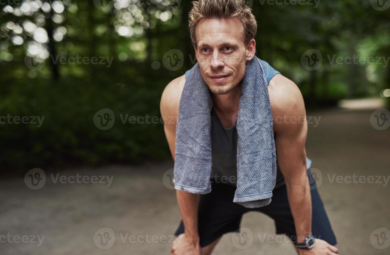 atletisk man vilar efter jogging i parken foto