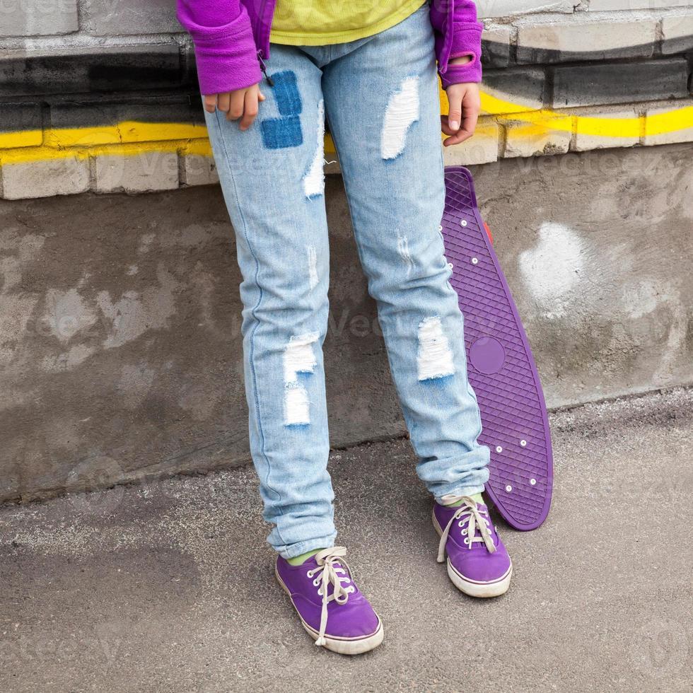 tonåring i jeans och gummiskor med skateboard foto
