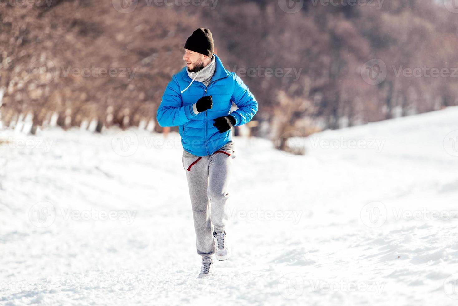 man springer och tränar på en snöig vinterdag foto