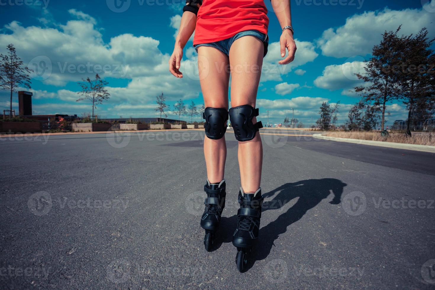 ung kvinna rullskridskoåkning på solig dag foto
