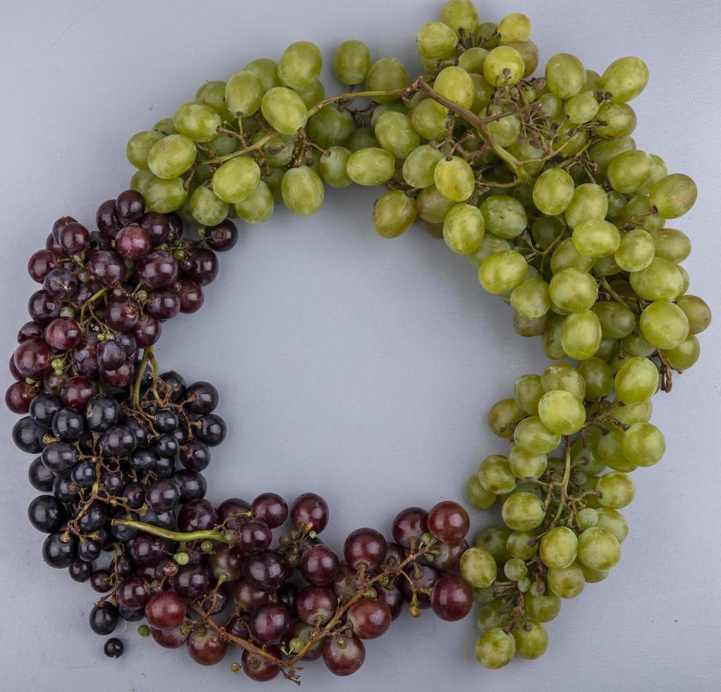 ovanifrån av druvor i rund form på grå bakgrund med kopieringsutrymme foto