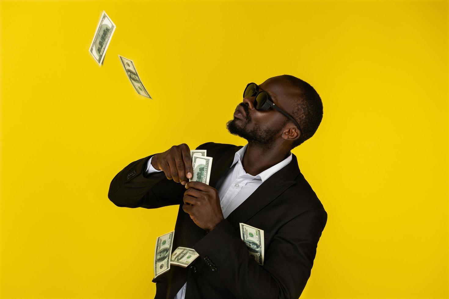en cool svart man kastar upp dollar foto