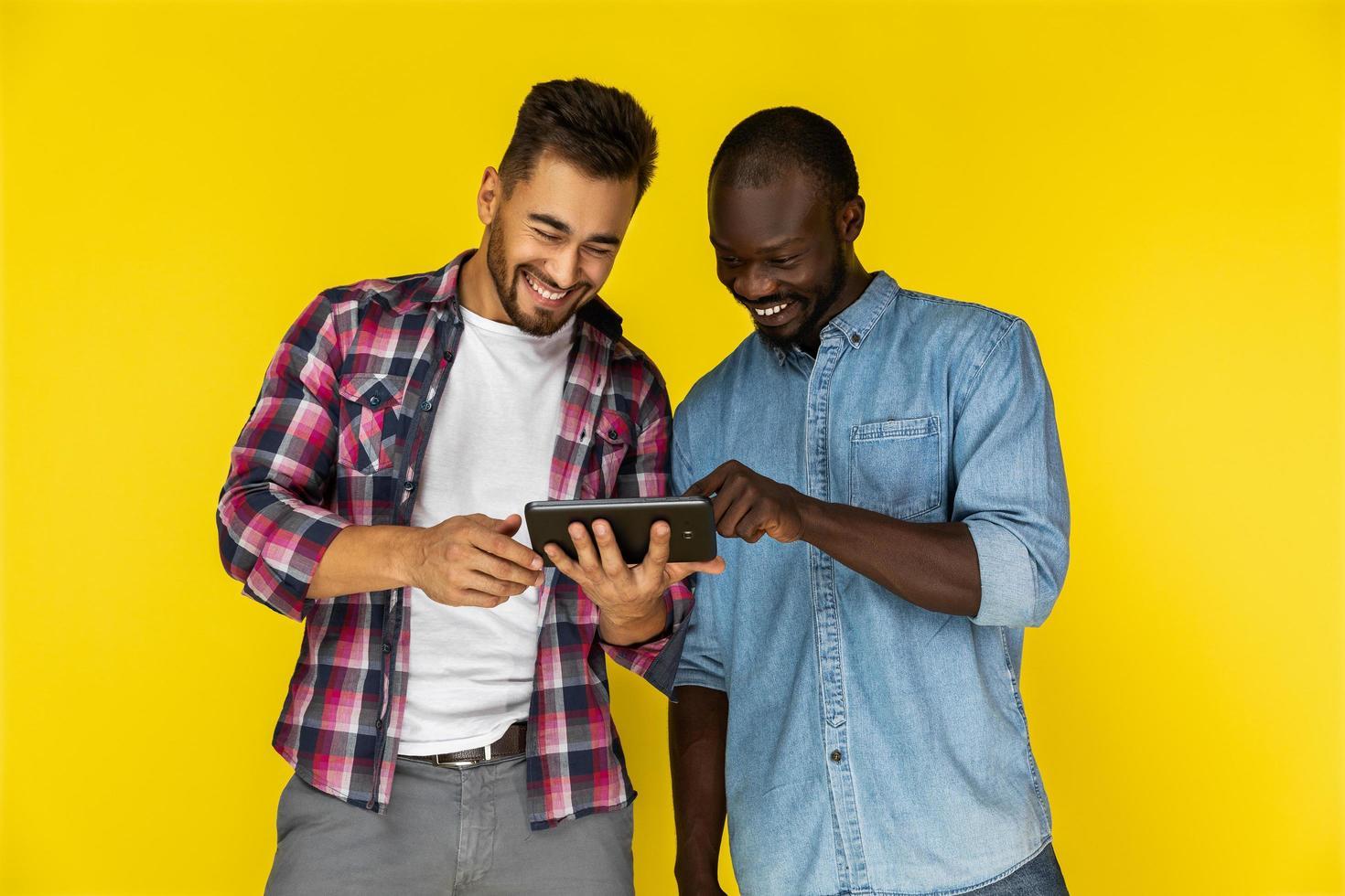 två män njuter av att titta på videor på surfplattan foto