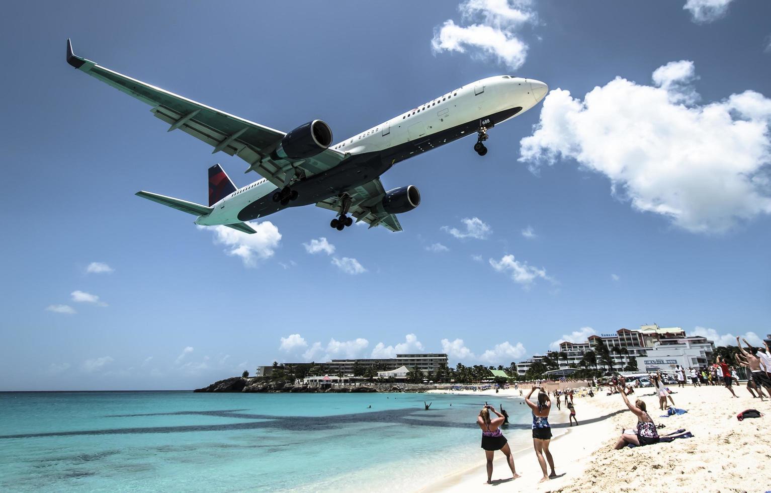 st. martin, 2013-turister tränger på maho beach när lågflygande flygplan närmar sig landningsbanan över strandlinjen foto