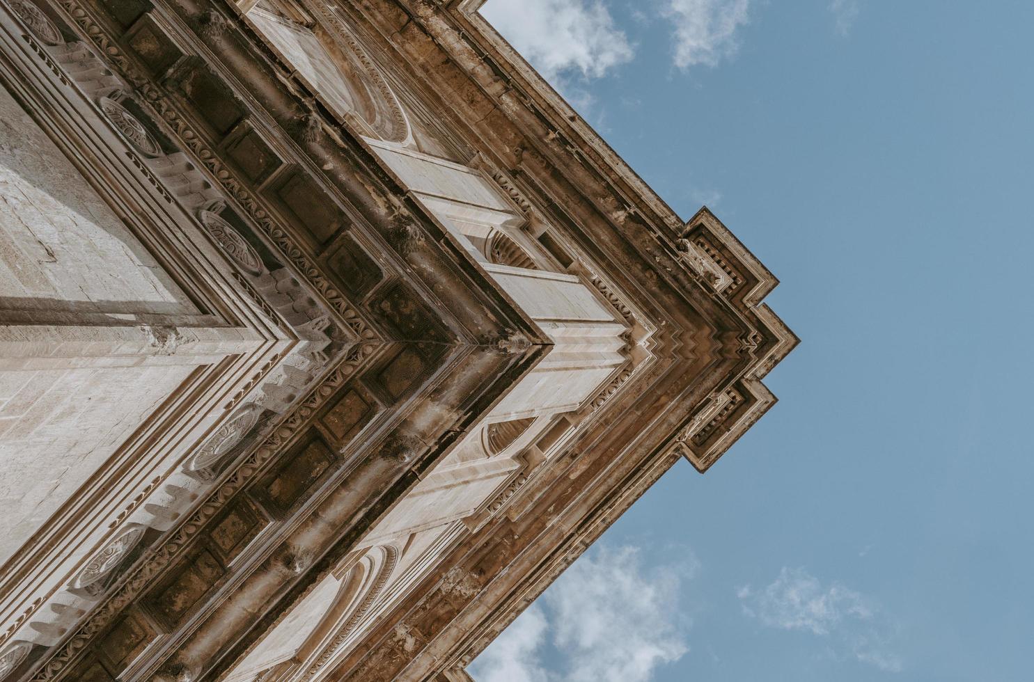 låg vinkel fotografering av beige byggnad under blå himmel foto