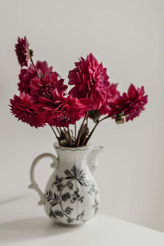 röda georginer i en vas foto