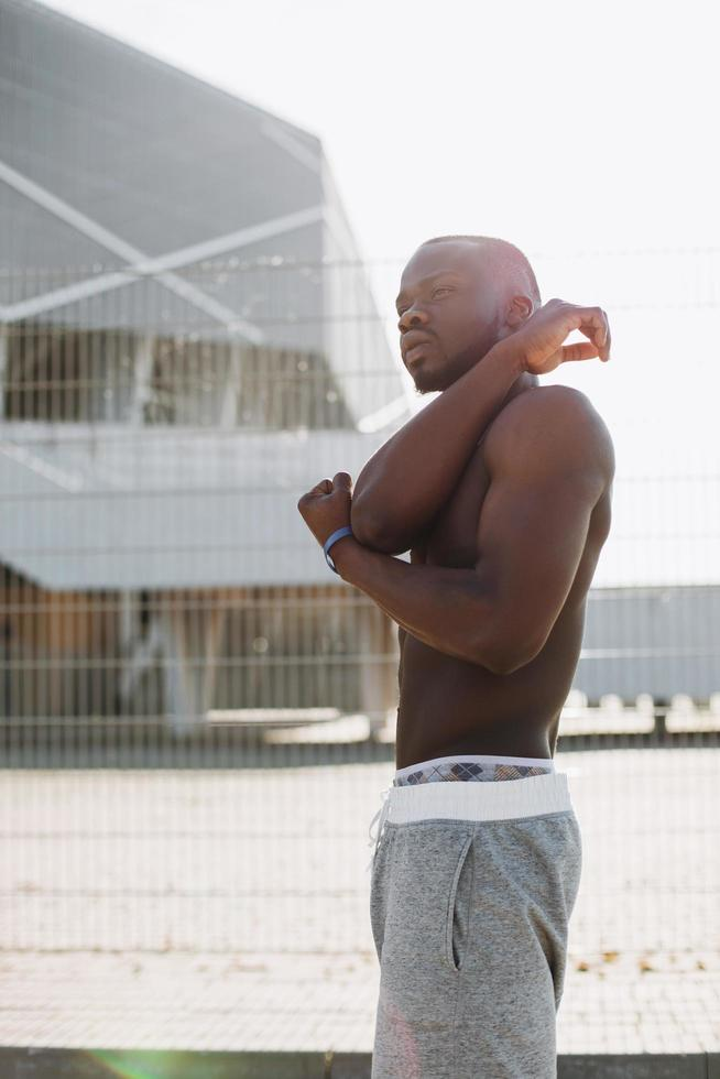 afroamerikansk man sträcker sig före en träning foto