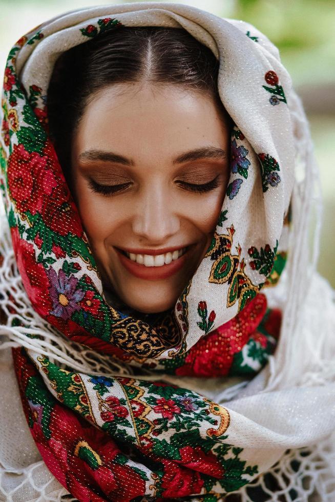 porträtt av en ung le flicka i en traditionell broderad klänning foto