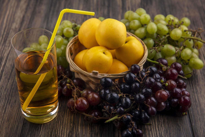 blandad frukt och glas juice på träbakgrund foto
