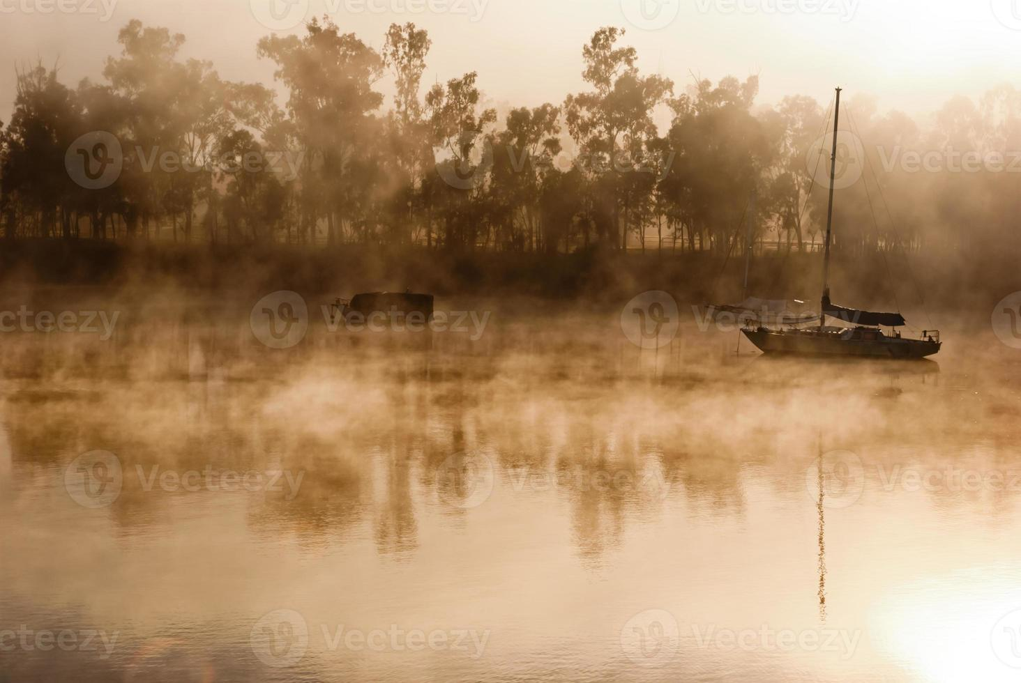 dimmig morgon på en flod med båtar foto