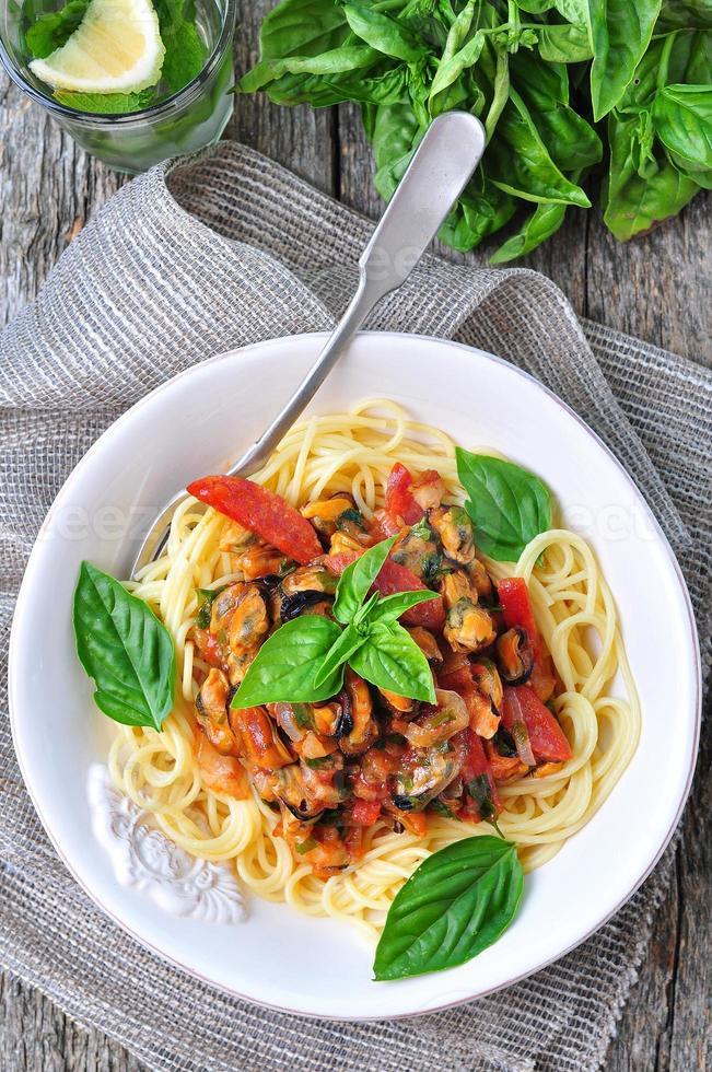pasta med musslor, pepperoni, bacon, tomat och basilika foto