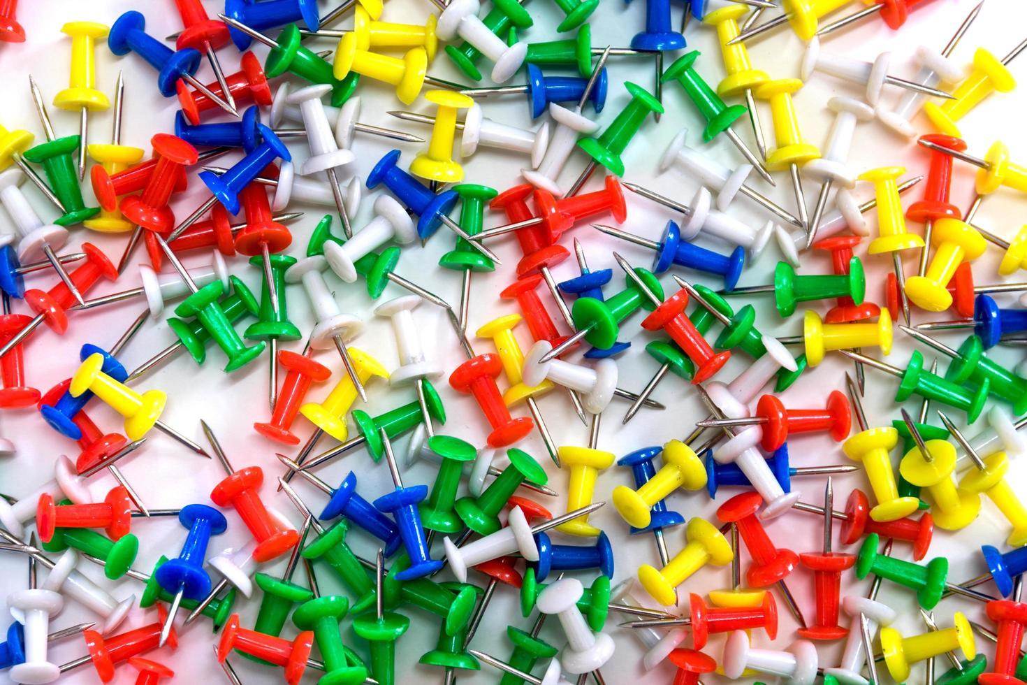 färgglada häftstift på vit bakgrund foto