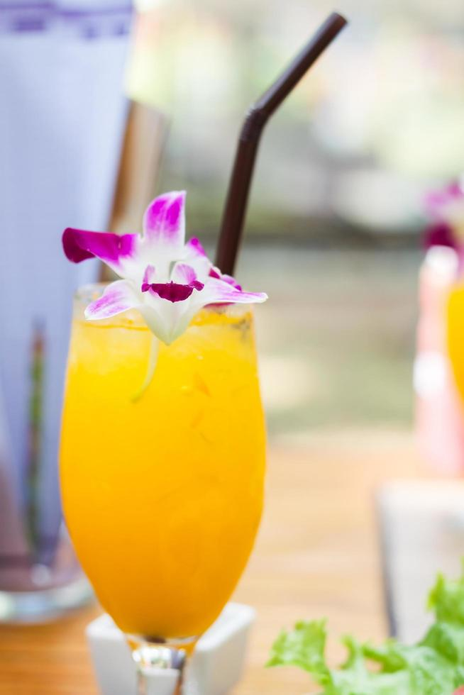 glas isad apelsinjuice med en blomma foto