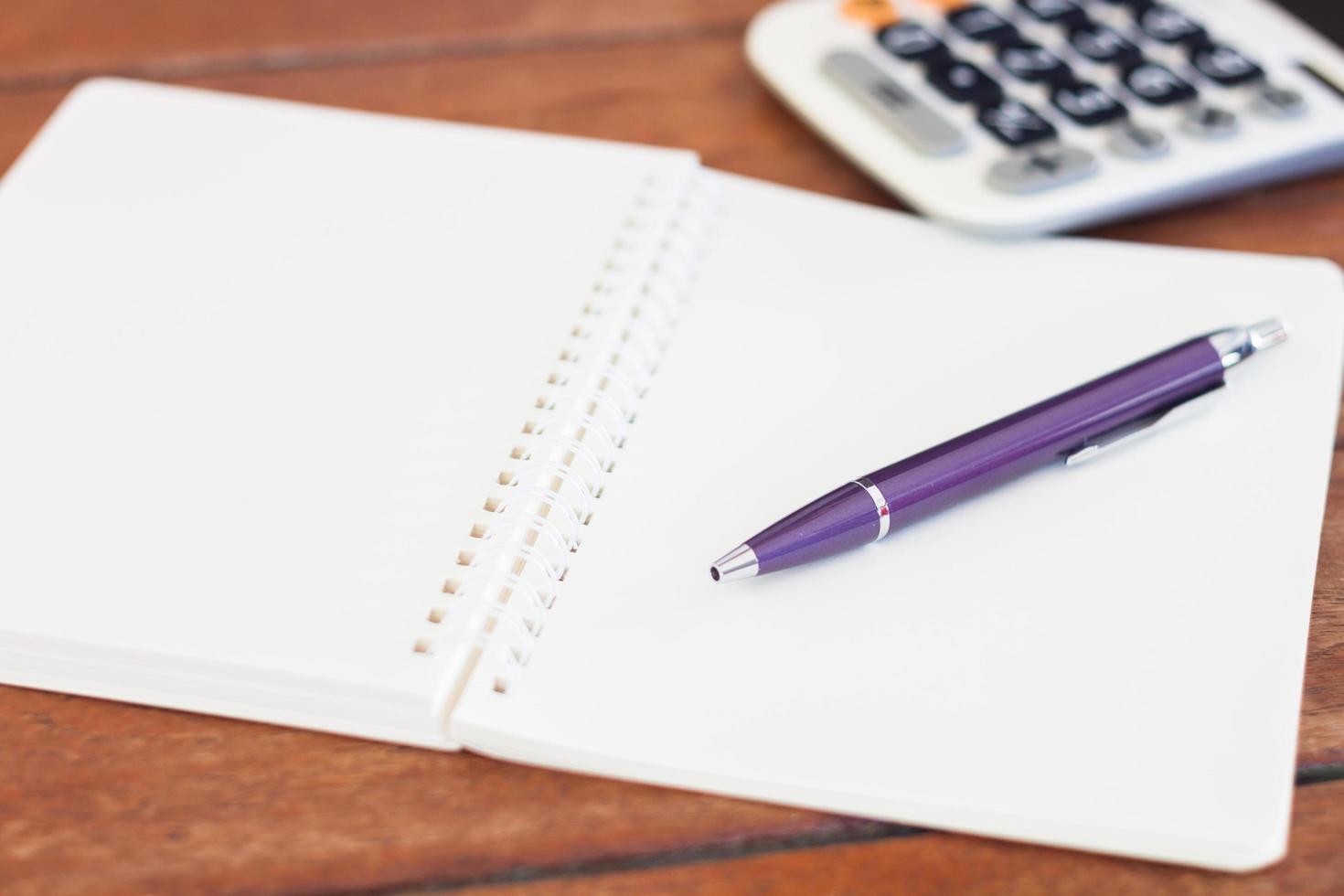 lila penna på en öppen anteckningsbok foto