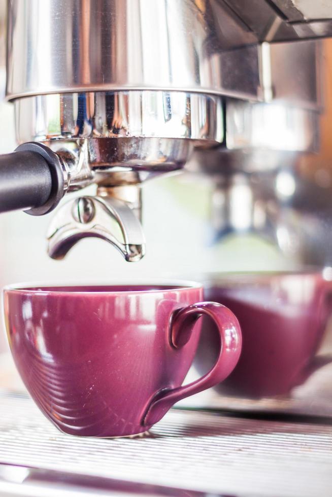 lila kopp under ett espressodropp foto