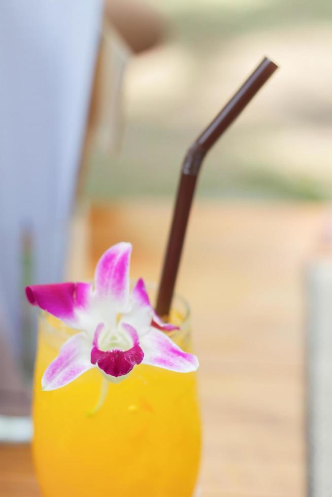 närbild av en orange cocktail med en blomma foto