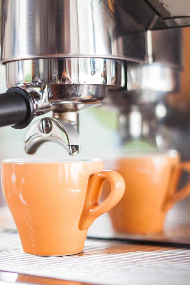 orange espressokopp under ett espressodropp foto