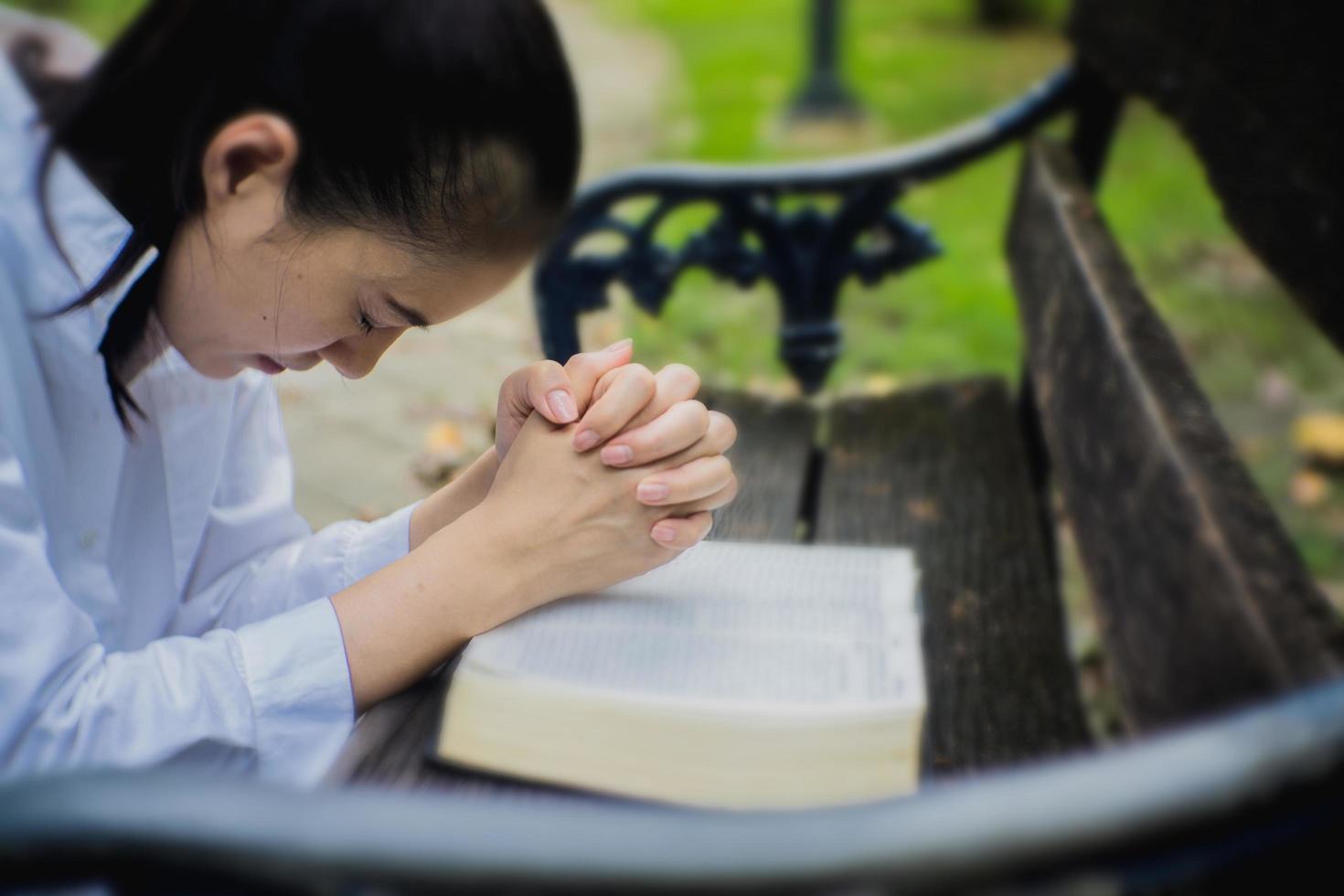 kvinnan ber med bibeln i trädgården foto