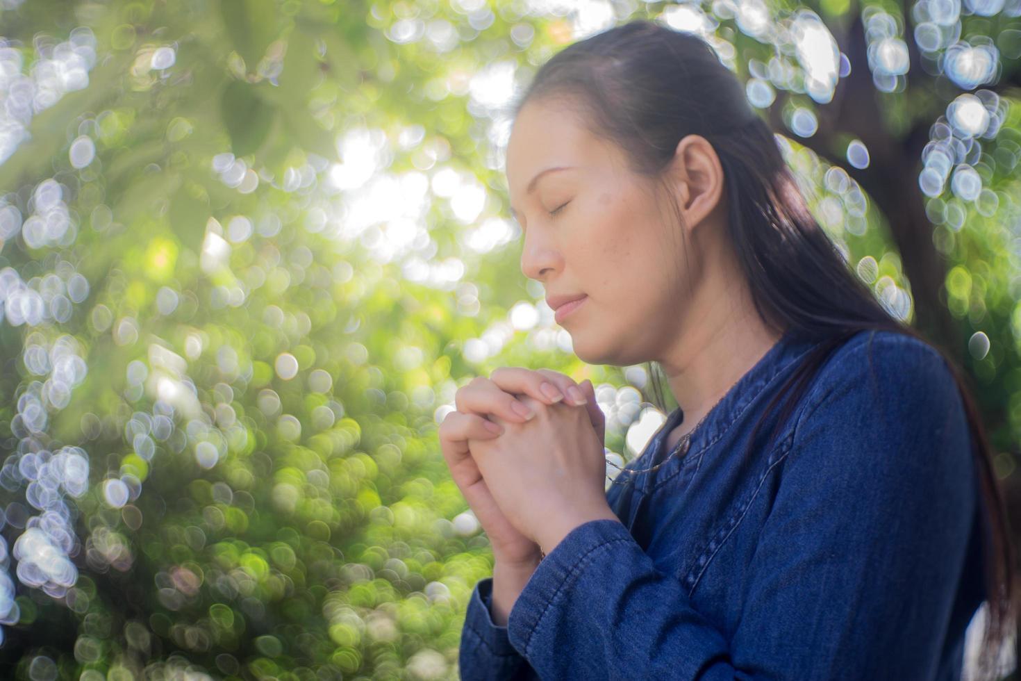 kvinna som ber i en trädgård foto