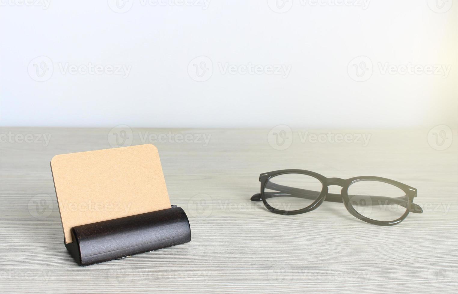 tomma visitkort och glasögon på träkontorsbord foto