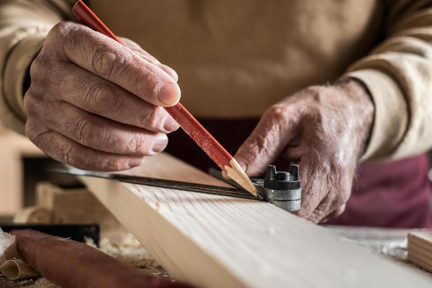 snickare som mäter en planka med en röd penna och en metalllinjal foto
