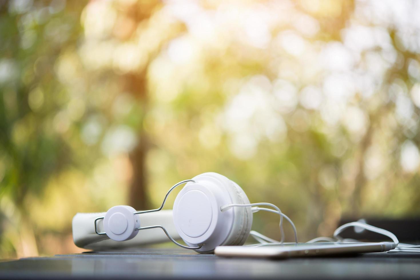 vita hörlurar på träbord med naturbakgrund foto