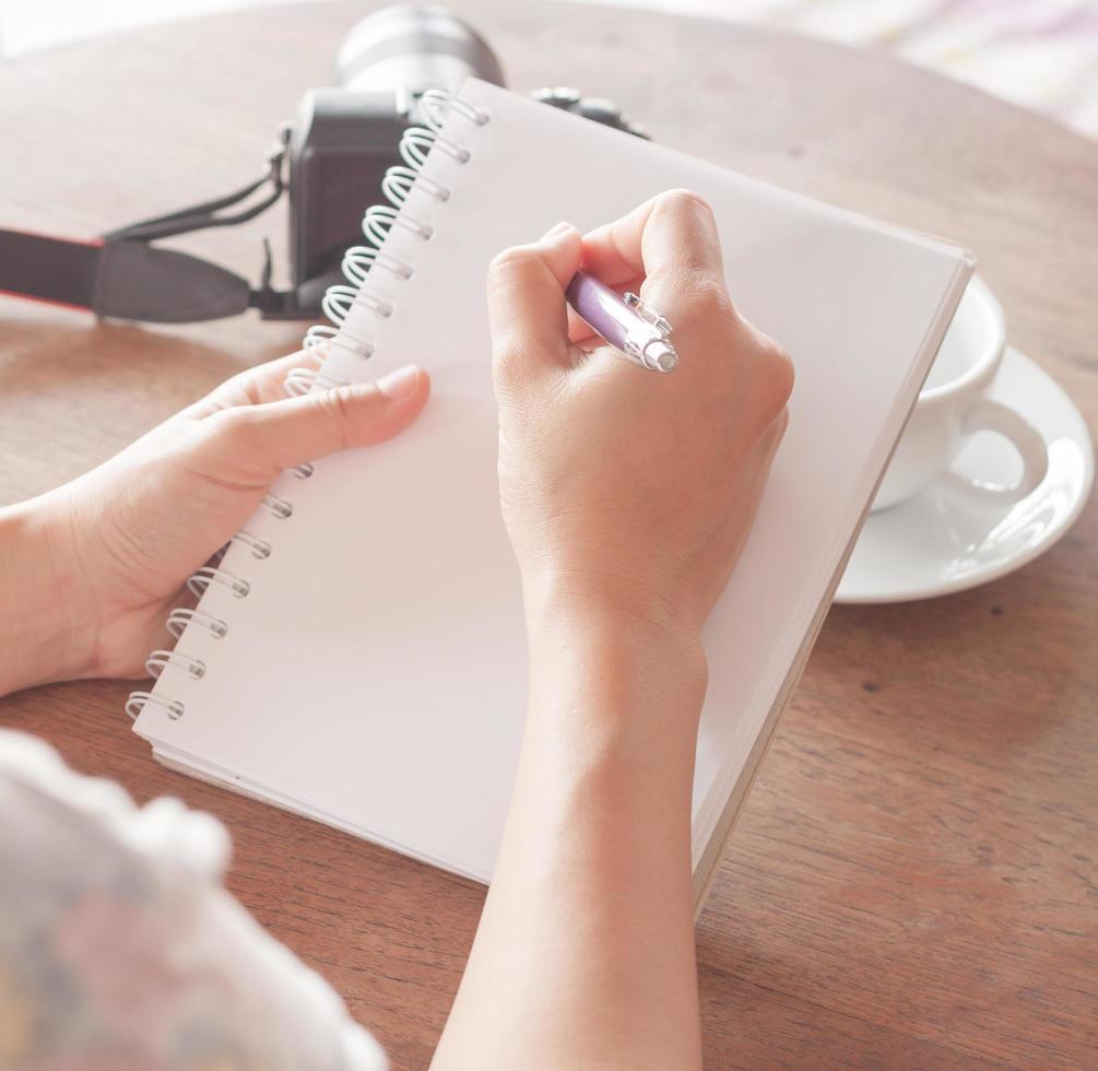 närbild av en kvinna som skriver i en anteckningsbok foto