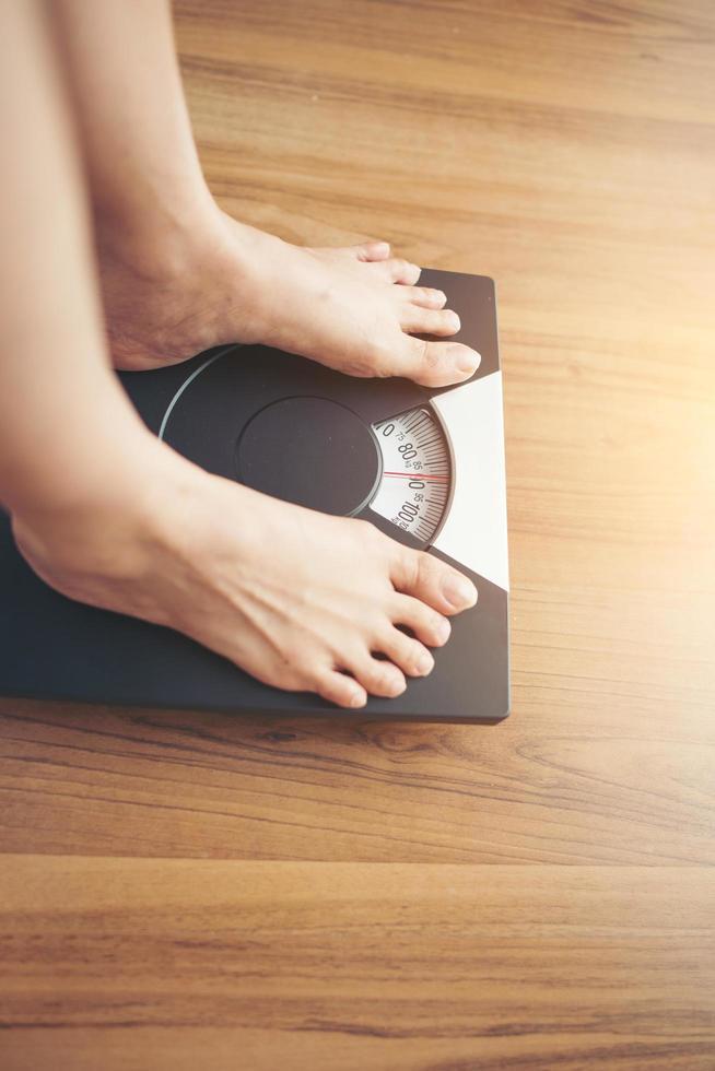 kvinnans fötter stående på vikt skala foto