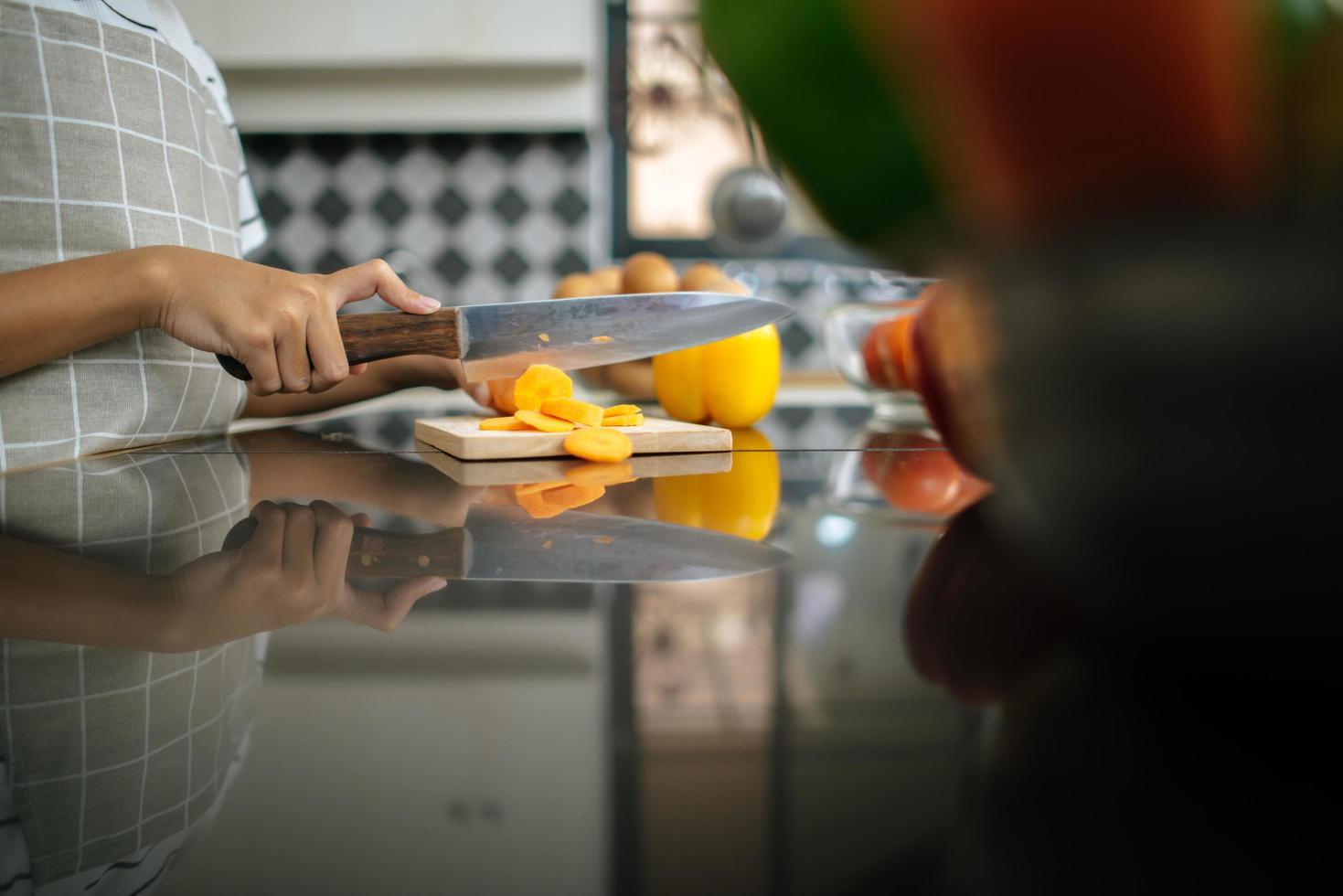närbild av flickahand som hugger gula paprika foto