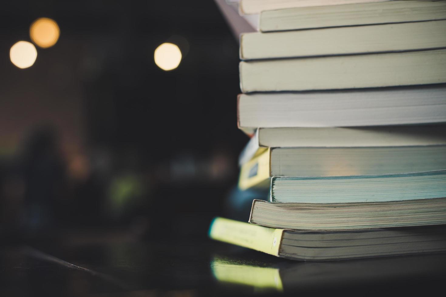 högar med böcker på ett bord över en suddig biblioteksbakgrund foto