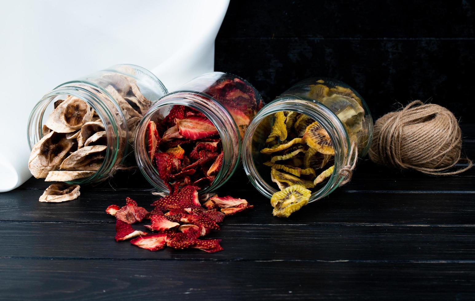 burkar med torkade fruktskivor med garn foto