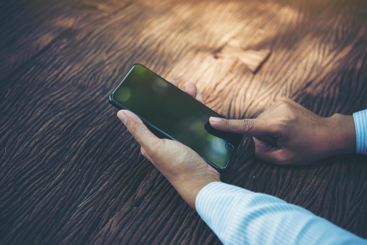 person som håller smart telefon vid ett bord foto
