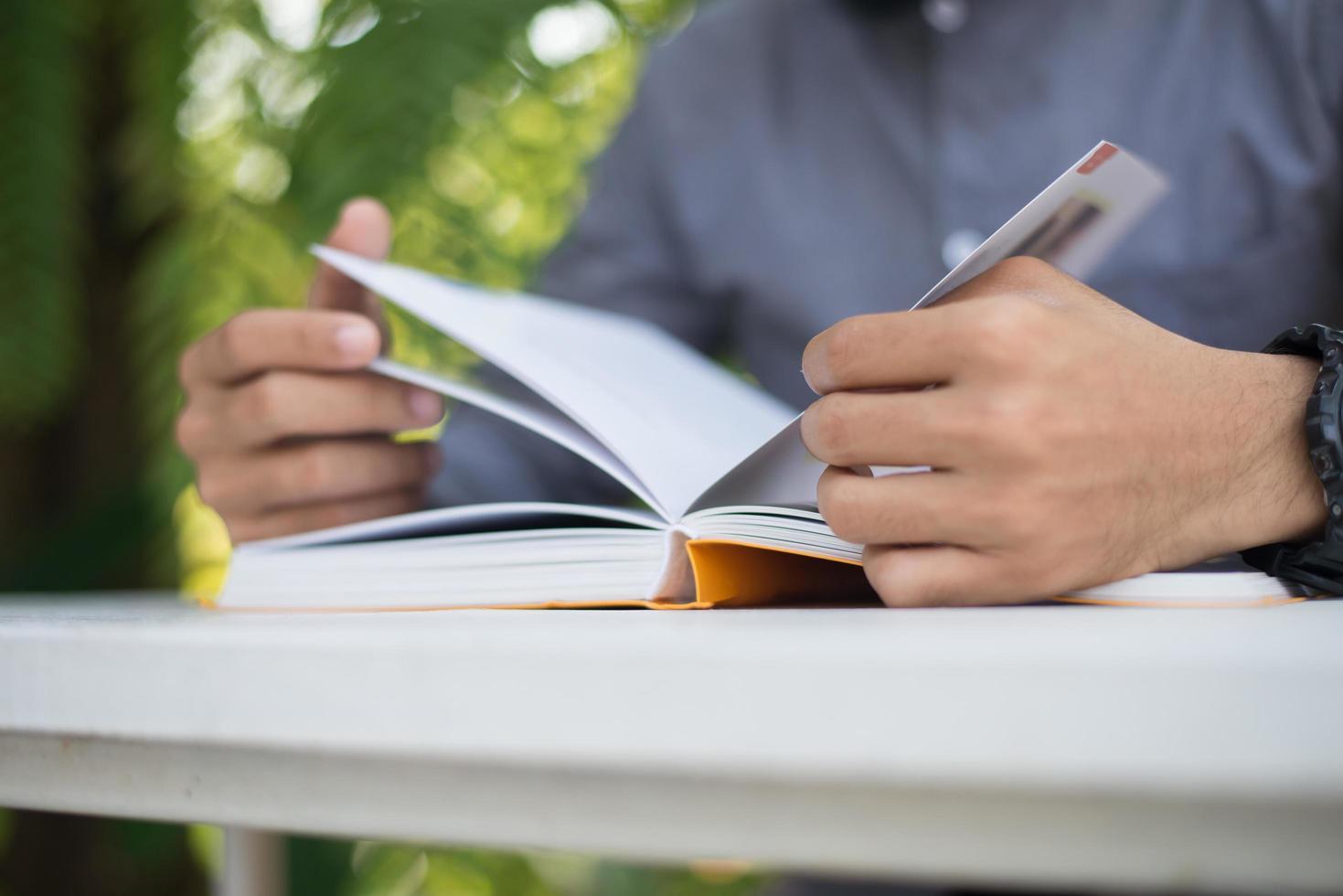 ung man läser böcker i hemträdgård med naturen foto