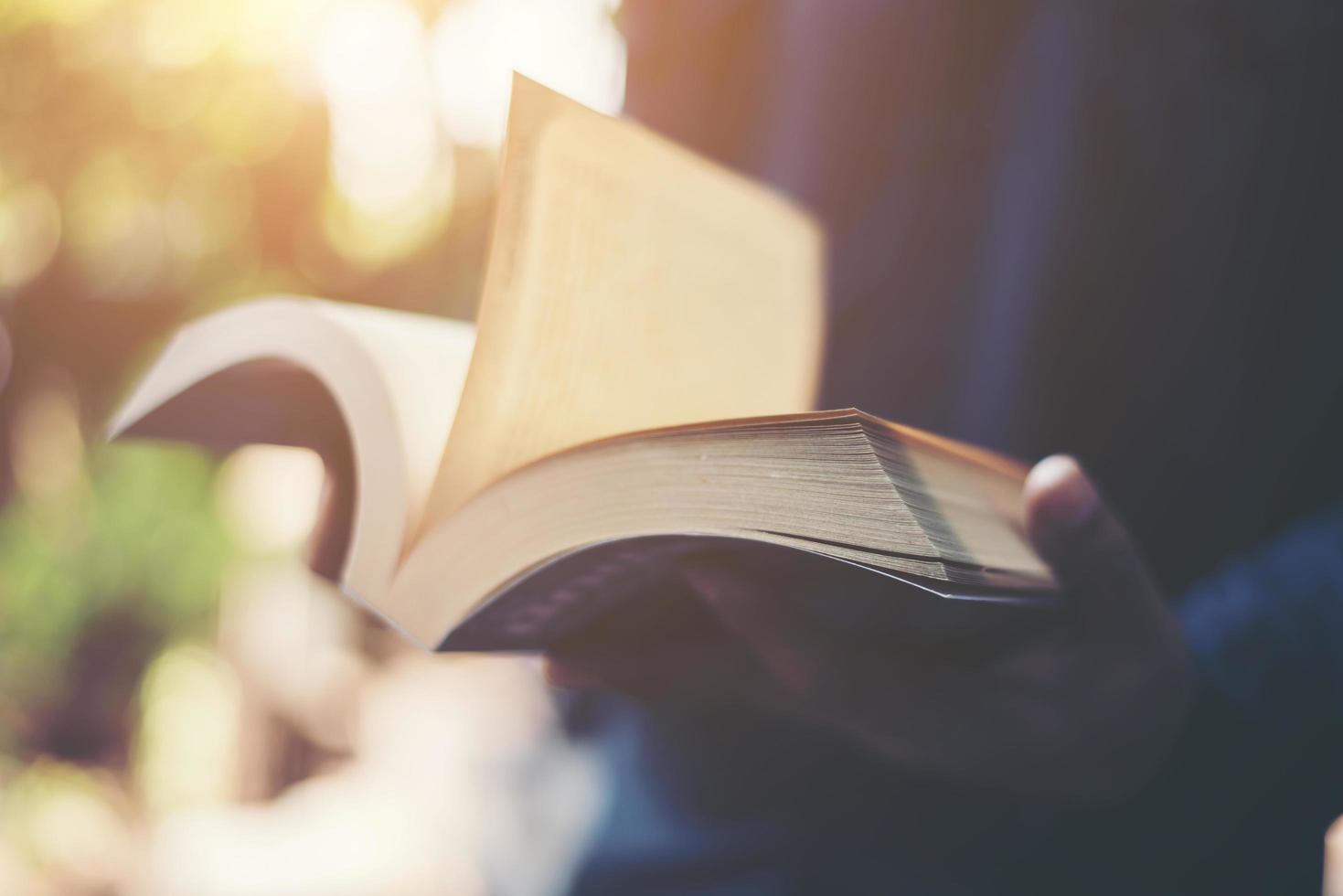 man som läser en bok i hans händer foto