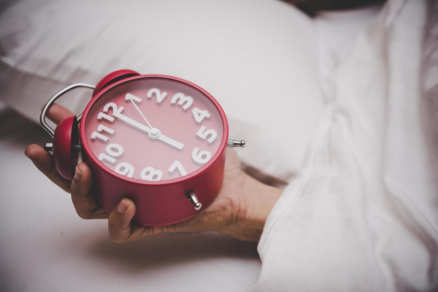 handen i sängen ställer in väckarklockan klockan 6 foto