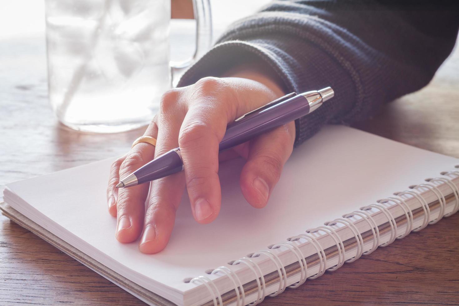 hand med en lila penna på en anteckningsbok foto